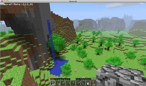 A lush new world in Minecraft. That grey pixelly bit at the front is a block of stone that I'm holding. But don't look at that - look at the incredible view and that awesome waterfall!