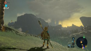 A screenshot of Breath of the Wild, with Link looking over a distant mountain vista. Large rainclouds can be seen looming in the sky.